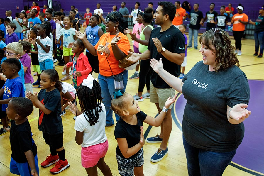 Kate Mashburn of Simpli.fi (right) sings with kids during a Camp Fort Worth summer camp event at Como Community Center in Fort Worth. Simpli.fi donated an iPad as one of the prizes for a summer reading program. (Smiley N. Pool/The Dallas Morning News)
