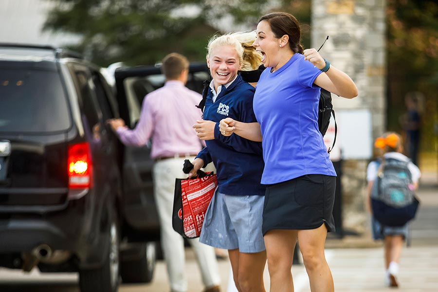 Teacher Kendall Hines (right) greets student Linda Bakich with a leaping side-bump as she gets out of the car in drop-off line before the start of school at Providence Christian School. (Smiley N. Pool/The Dallas Morning News)