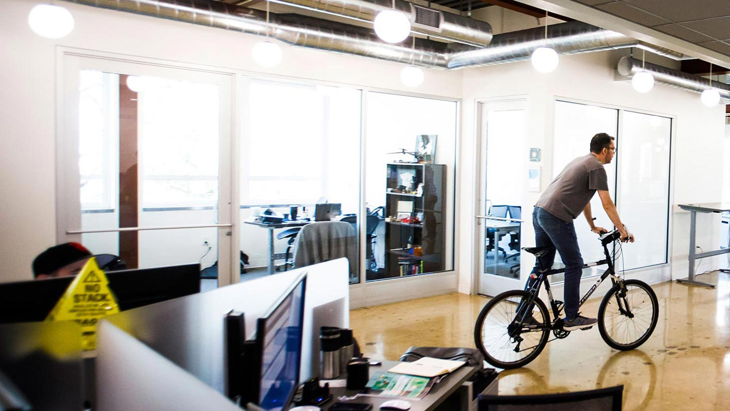 Bike Craig Bowes, director of Application Development, rides his bike through the office to his desk at Simpli.fi offices on Wednesday, Sept. 6, 2017, in Fort Worth. (Smiley N. Pool/The Dallas Morning News)